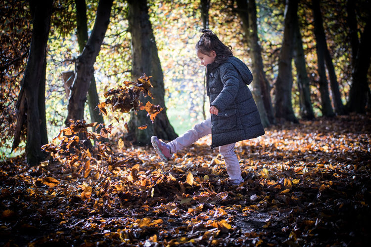 Girl kicking leaves in forest