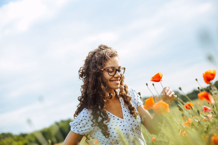 young woman with curly hair enjoying the freedom of the summer and some leisure time in the countryside Beautiful Adult Beauty In Nature Countryside Enjoyment Flower Flowering Plant Front View Glasses Hair Hairstyle Happiness Leisure Activity Long Hair Nature One Person Outdoors Plant Sky Smiling Summer Warm Women Young Adult Young Women