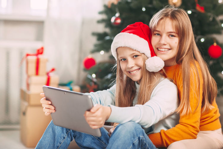 Portrait of smiling young woman sitting on christmas tree