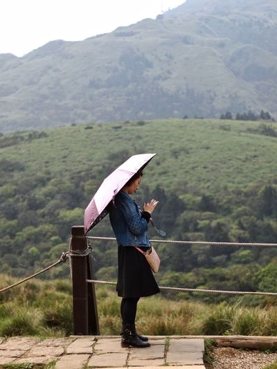 Side view of young woman with umbrella standing against mountains