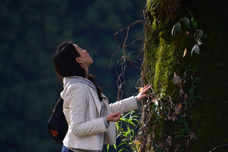 Woman standing against moss wall
