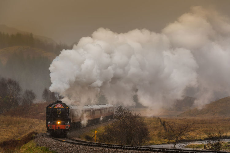 HogwartsExpress - The Jacobite - in the Scottish Highlands on a rainy but magic day this December. **This edit was inspired by J.M.W. Turner's 'Rain, Speed and Steam' which I love so much. More soon. Harry Potter Hogwarts Rain Scotland Hogwarts Express Landscape Locomotive Mode Of Transport Moody Nature No People Smoke - Physical Structure Steam Steam Train Train - Vehicle Transportation Tree EyeEm Ready