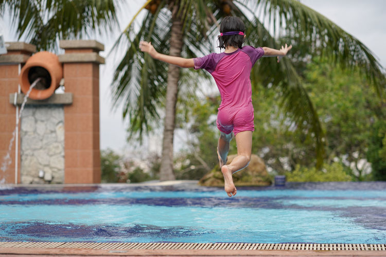 Kid jumping into the swimming pool Kid Holiday Fun Asian  Swim Girl Full Length Swimming Pool Water Tree Summer Jumping Wearing Diving Stunt
