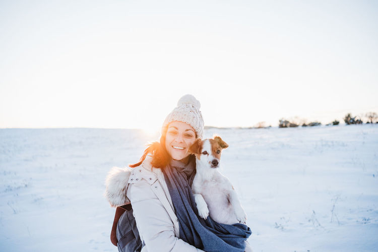 Portrait of smiling woman with dog on snow covered land against sky