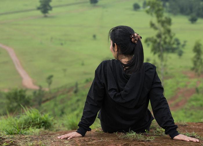 Rear view of woman relaxing on field