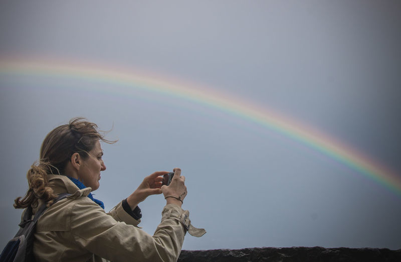 Woman photographing rainbow against sky