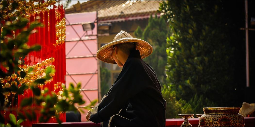 Man wearing conical hat while sitting in temple