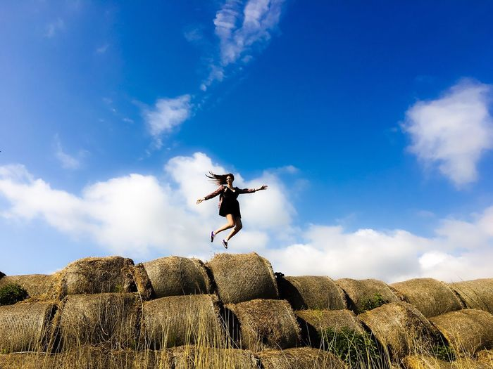 Low Angle View Of Excited Woman Jumping Over Hay Bales On Field Against Sky