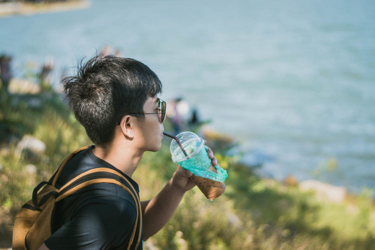 Young man having drink by sea