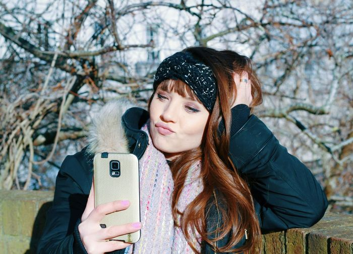 Woman taking selfie against bare trees