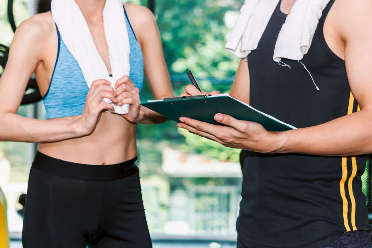 Midsection of woman with instructor standing in gym