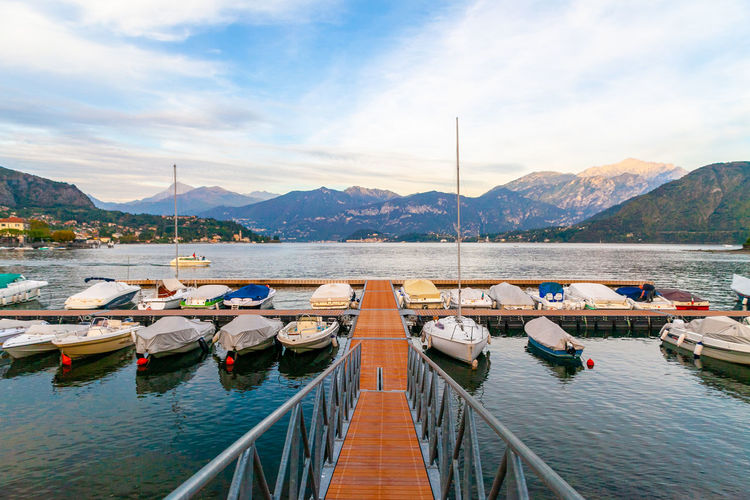 A harbour with boats and pier on lake of como, lombardy, italy at sunset