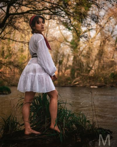 Full length of woman standing by water