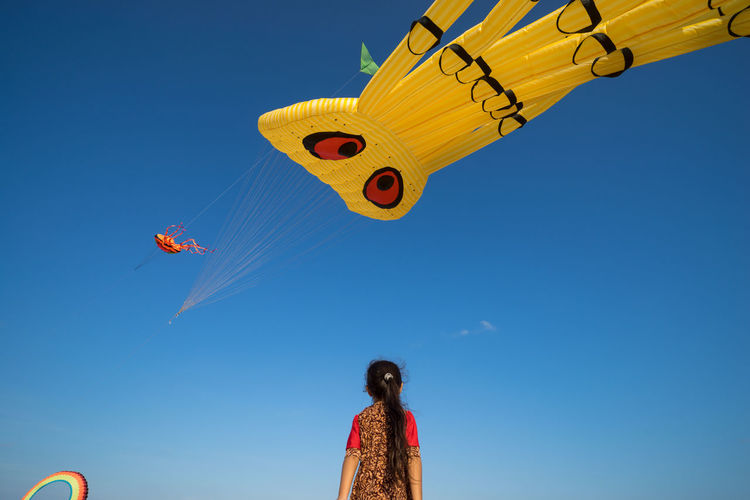 Low Angle View Of Girl Looking At Kites Flying In Clear Blue Sky During Festival