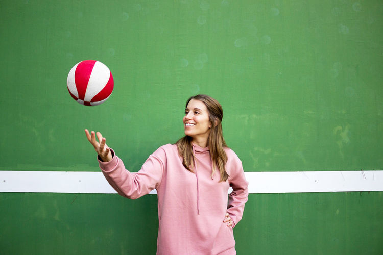 Smiling young woman tossing basketball while standing against wall