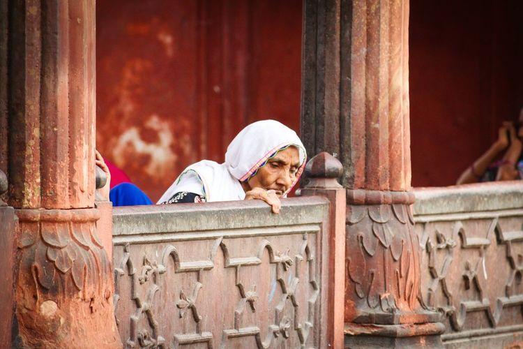 Senior woman by retaining wall at jama masjid