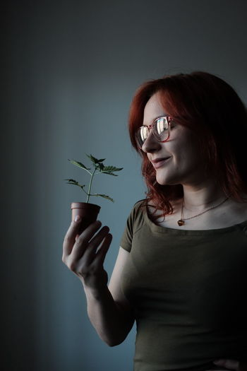 Midsection of woman holding eyeglasses while standing against plants