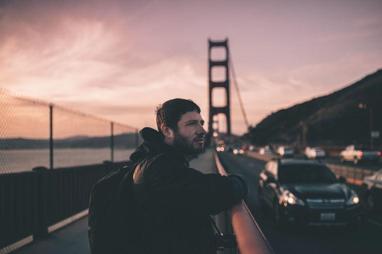 Side view of man on golden gate bridge during sunset