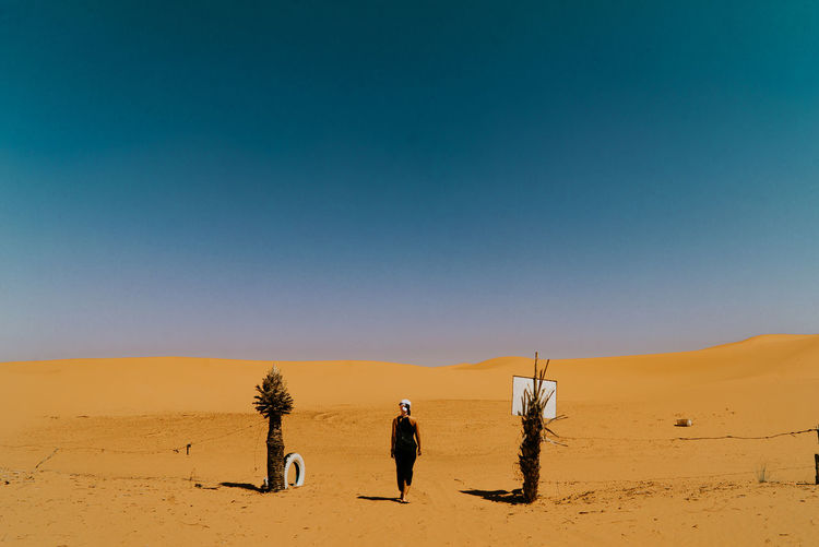 A young women standing on the gate on desert against clear sky