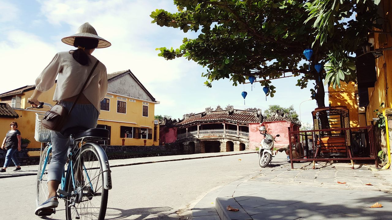 built structure, architecture, building exterior, outdoors, real people, transportation, day, bicycle, tree, men, sky, one person, people