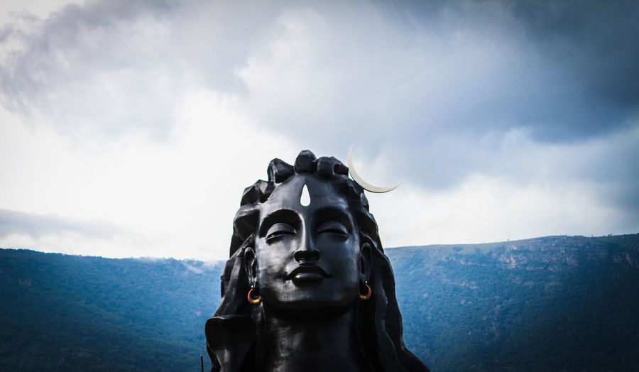 Low angle view of shiva statue against sky