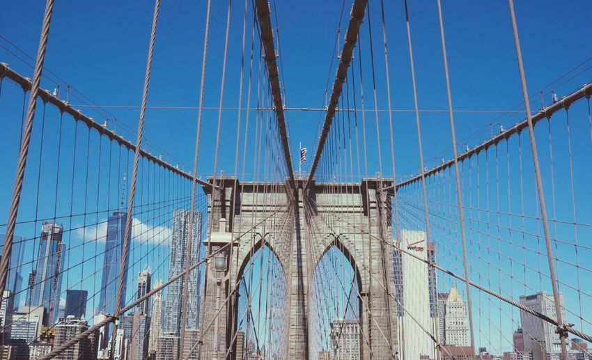 Low angle view of suspension bridge against blue sky