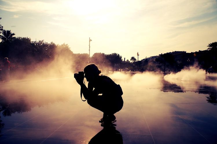 Side view of a silhouette female photographer