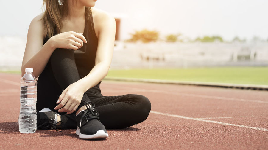 Low Section Of Woman Sitting On Sports Track