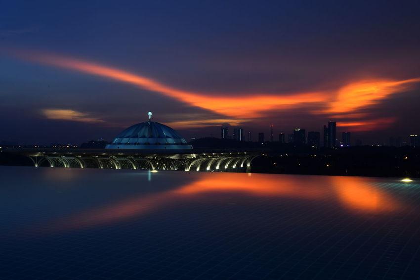 Dome of Tuanku Mizan Sultan Zainal Abidin mosque view from rooftop swimming pool. Mosque City Cityscape Urban Skyline Illuminated Sunset Dome Sea Water Skyscraper