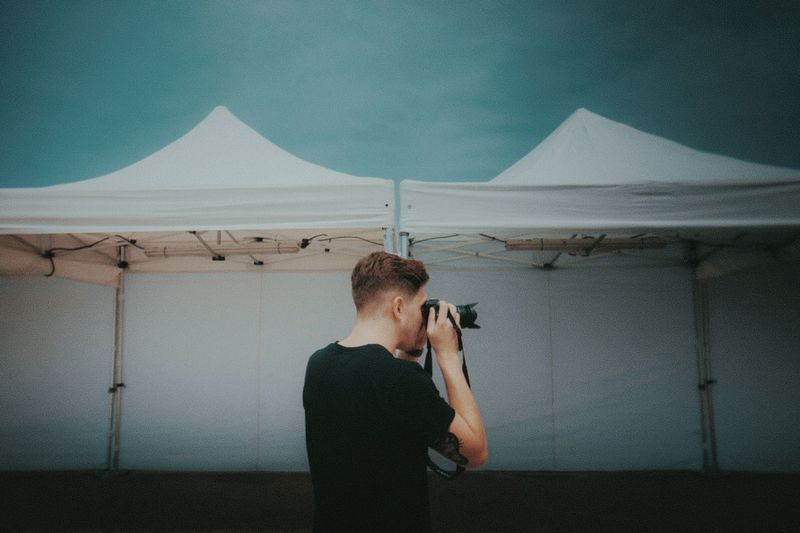 Rear view of young man photographing while standing by tent against sky