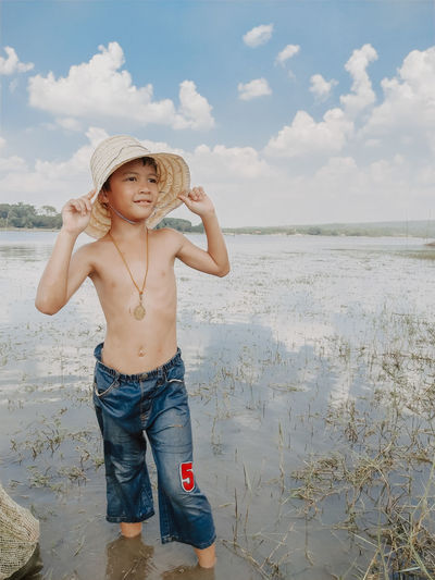 Close-up of cute shirtless boy standing in water against sky