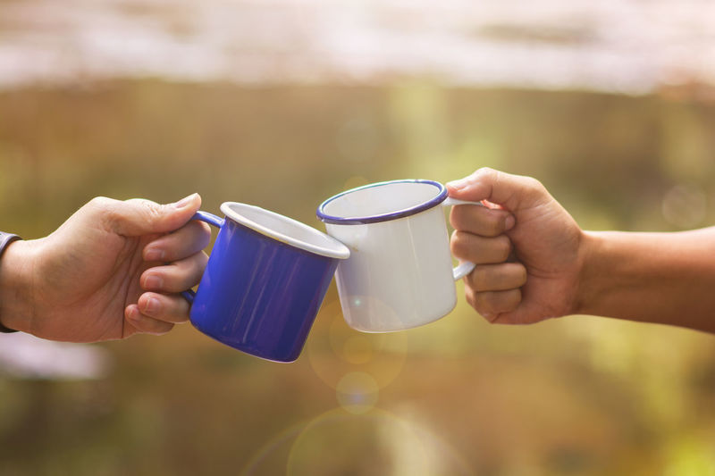 Clink glasses a cup of coffee together in the wild, blur background with sun flares Body Part Cup Day Drink Finger Focus On Foreground Food And Drink Hand Holding Human Body Part Human Hand Human Limb Lifestyles Limb Men Mug People Real People Refreshment Tea Cup Two People
