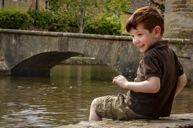 Side view of smiling boy sitting by lake