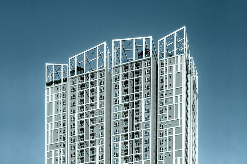 Low angle view of modern apartment building against clear blue sky