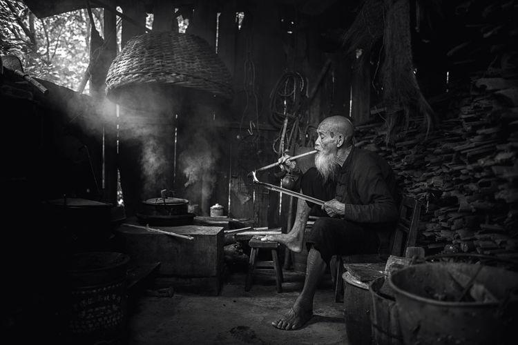 Senior man smoking at home