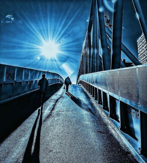 Man walking on bridge in city against sky