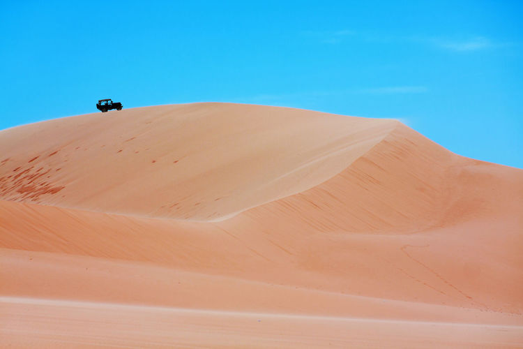 Sand dune in desert against blue sky