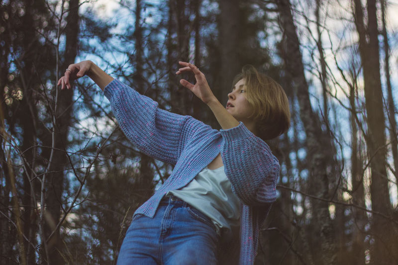 Young woman with short hair dancing against trees in forest
