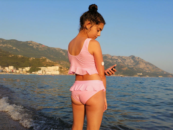 Life with diabetes. girl checks glucose level before enters the sea with cgm device
