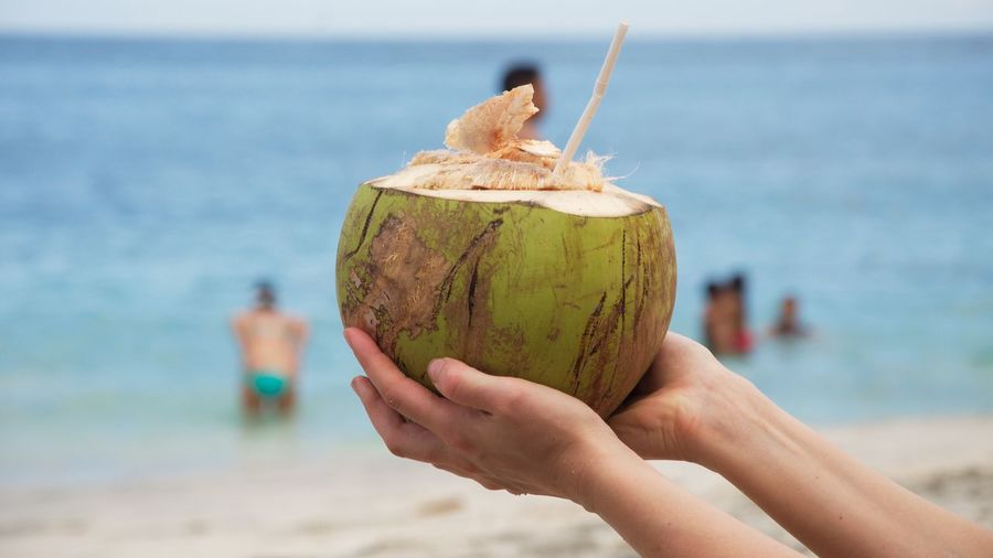 Cropped image of person holding coconut at beach