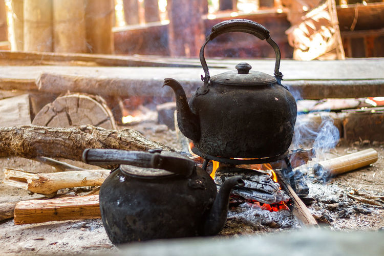 Close-up of teapots on wood burning stove
