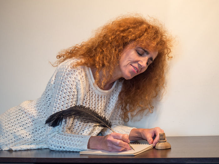 Woman looking away while sitting on table
