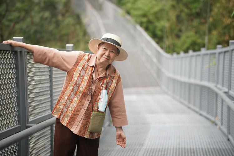 Portrait of woman standing against railing