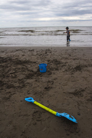 Sand Pail And Shovel Childhood Child Real People Leisure Activity Boys Will Be Boys Boy At The Beach Boy Playing In The Beach Boy Playing Kid Photography Caspian Sea Iran Chaboksar Beach Water Sea Sand Nature Full Length Bucket Lifestyles Sky Trip Vacations Sea And Sky