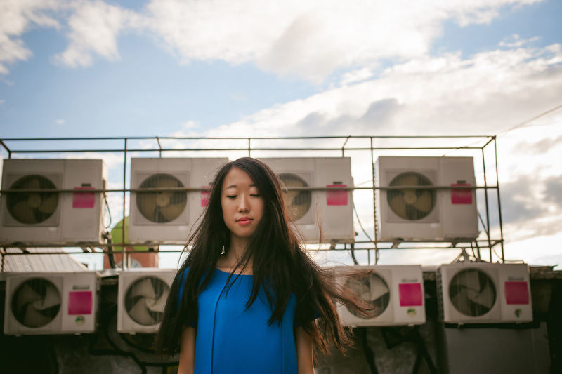 Young Woman Standing Against Air Conditioners And Sky