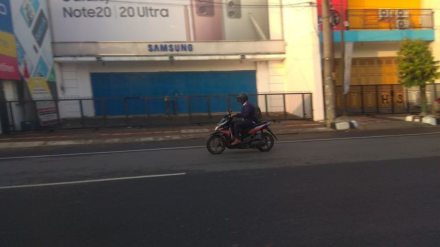 Man riding motor scooter on road by buildings