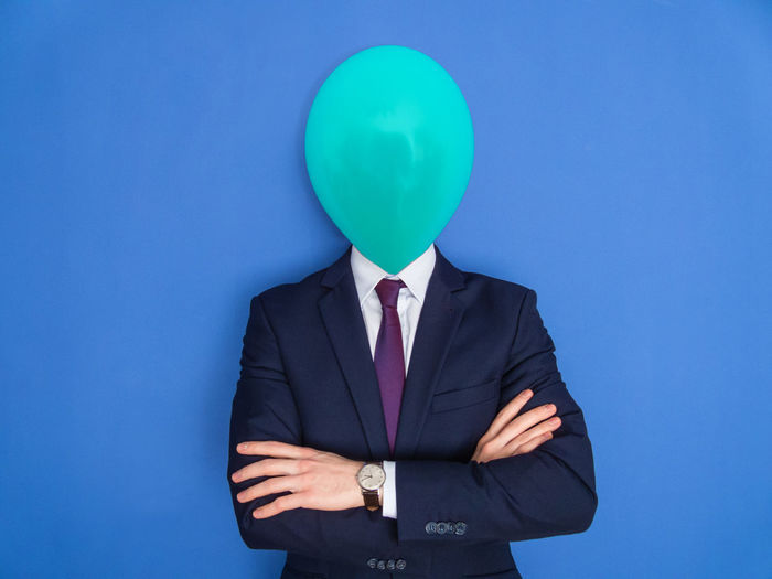 Face of businessman covered with balloon against blue background