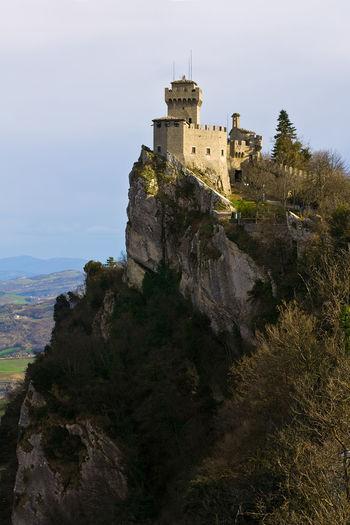 Castle on hill against cloudy sky