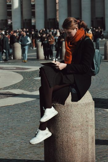 Side view of woman studying while sitting on column in city
