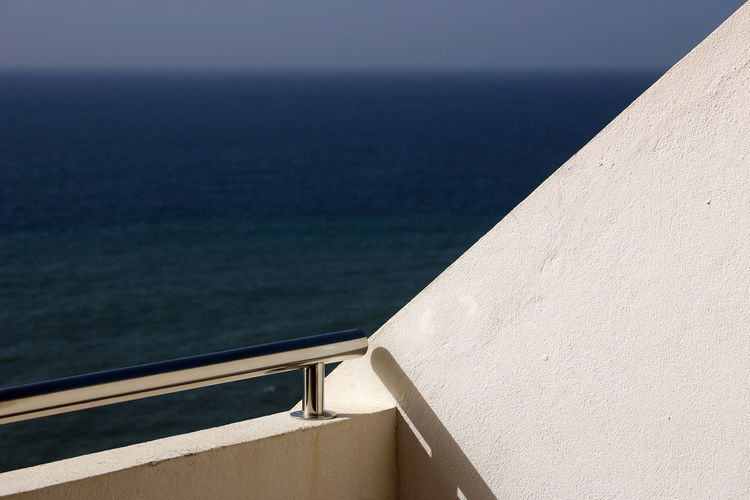 Close-up of retaining wall by sea against sky